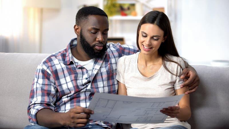 Jeune famille multiraciale regardant le plan de bâtiment, choisissant la conception intérieure images stock