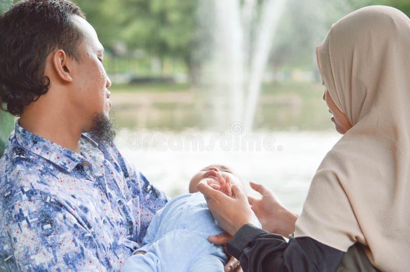 Jeune famille musulmane avec le bébé en parc extérieur près de lac avec la fontaine d'eau au temps de jour photos libres de droits