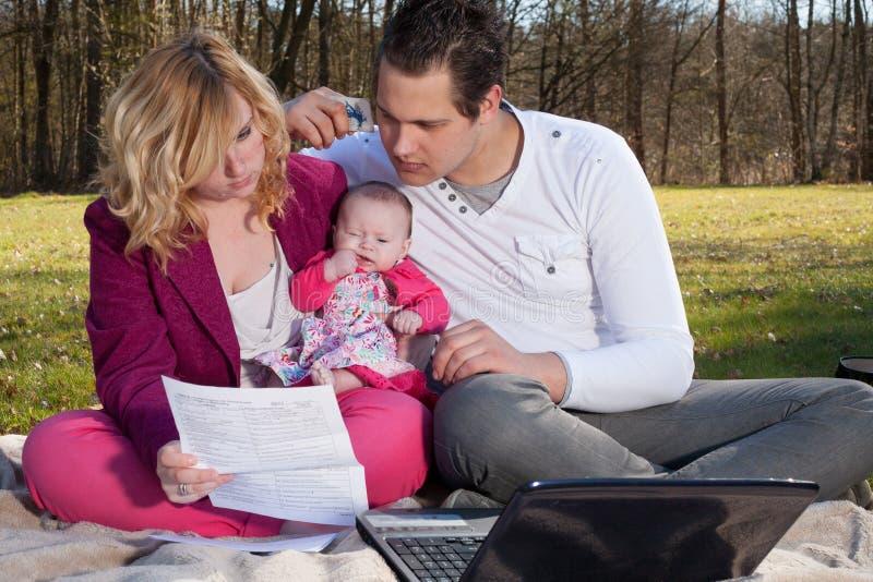 Jeune famille occupée avec des finances images libres de droits