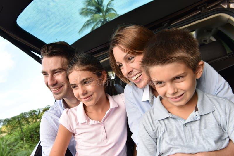 Jeune famille s'asseyant dans le tronc de voiture se sentant heureux images stock