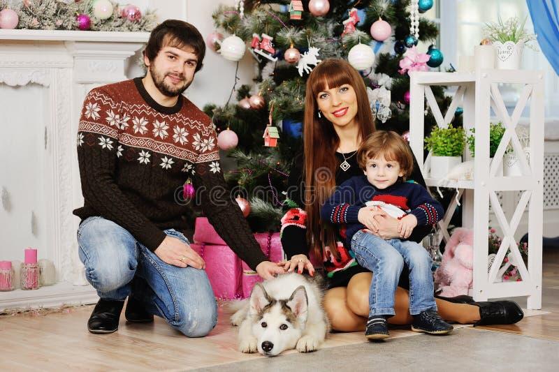 Jeune famille s'asseyant sous l'arbre de Noël photographie stock libre de droits