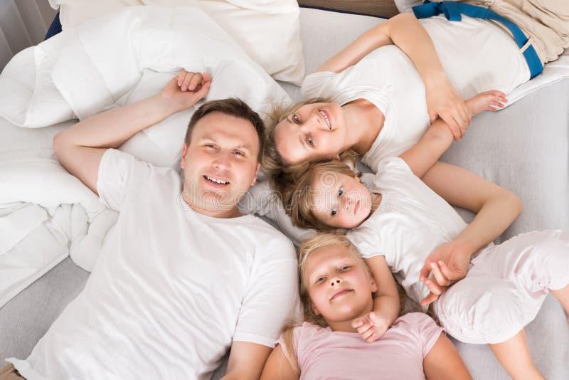 Jeune famille se situant ensemble dans le lit photos libres de droits