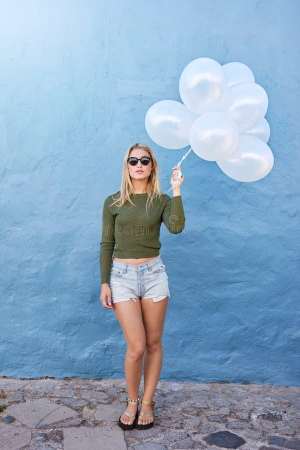 Jeune femelle à la mode tenant des ballons photo stock