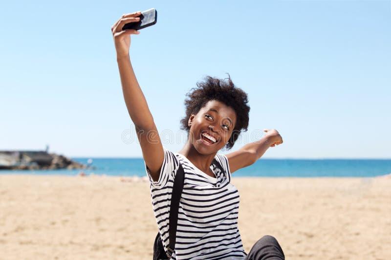 Jeune femelle afro-américaine de sourire sur la plage et le selfie parlant photographie stock libre de droits