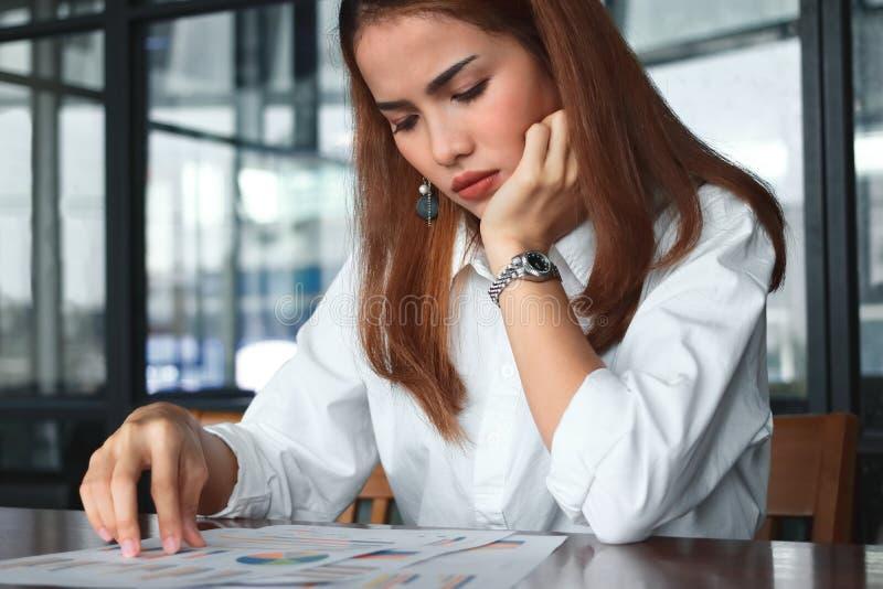 Jeune femelle asiatique soumise à une contrainte fatiguée d'affaires analysant des diagrammes ou le rapport sur le lieu de travai photo libre de droits