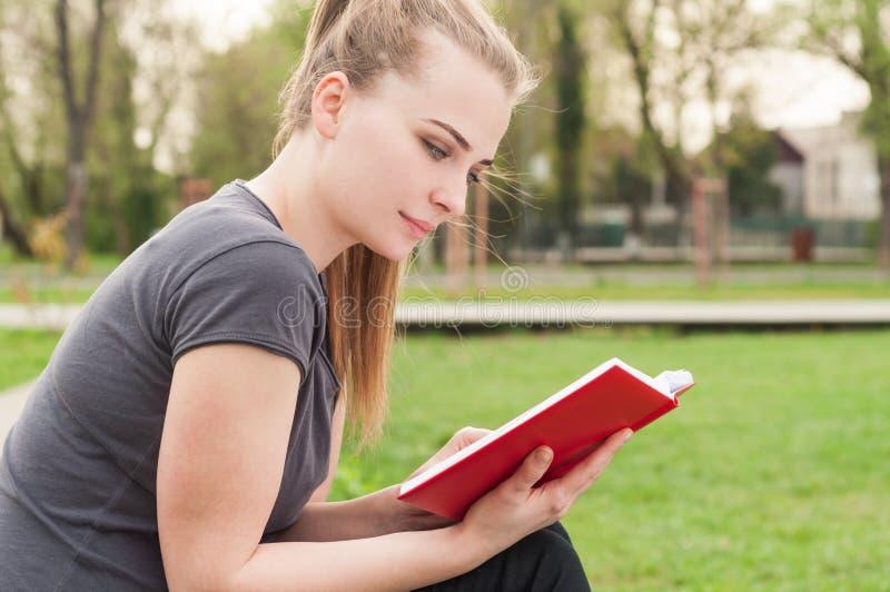Jeune femelle attirante reposant et lisant un livre photographie stock libre de droits
