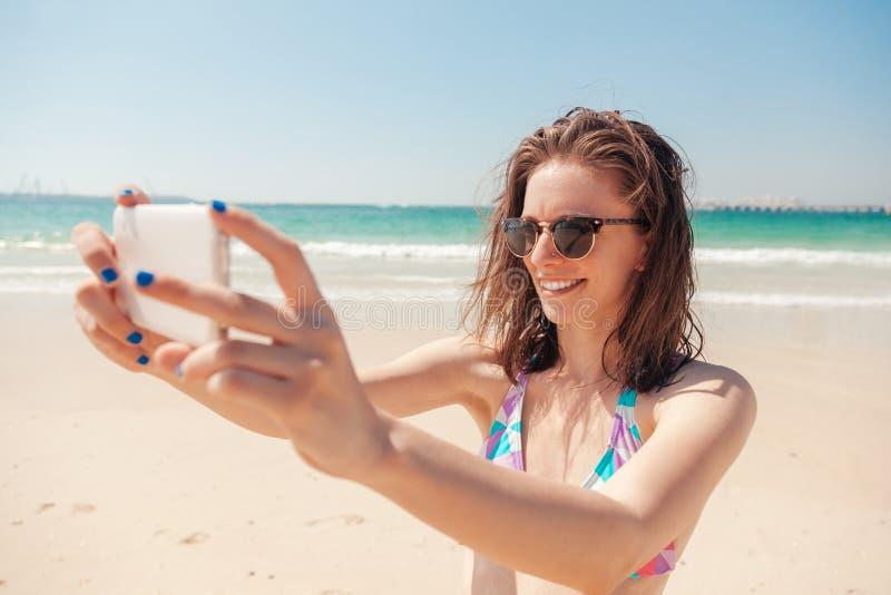 Jeune femelle au bord de la mer prenant Selfie images stock
