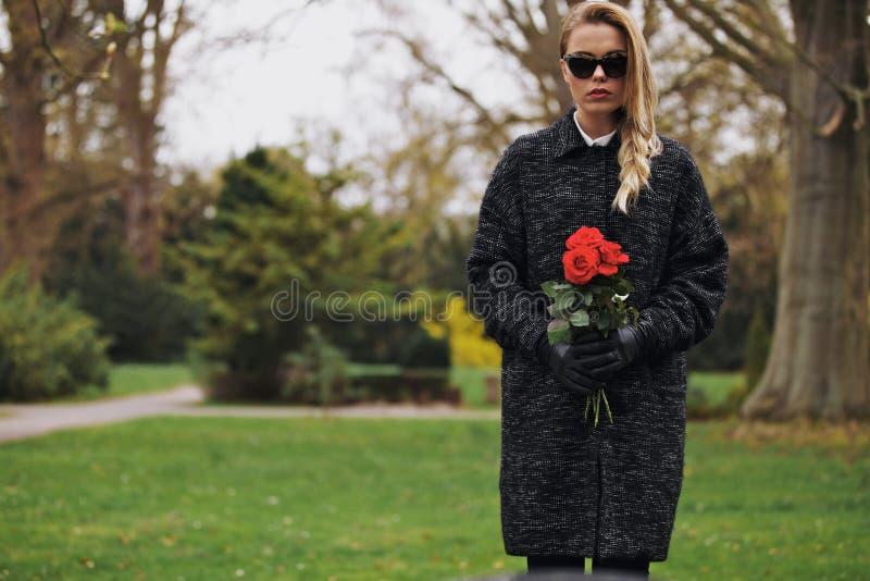 Jeune femelle au cimetière avec les fleurs fraîches images libres de droits