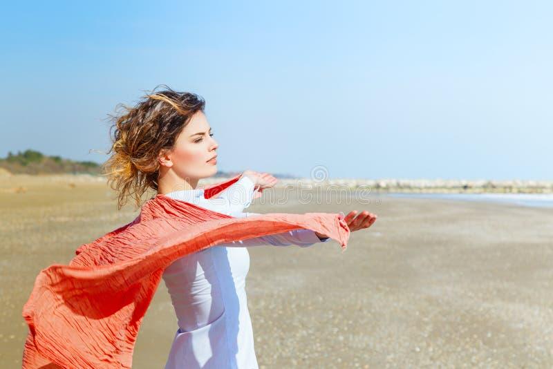 Jeune femelle avec l'écharpe rouge sur la plage photo libre de droits