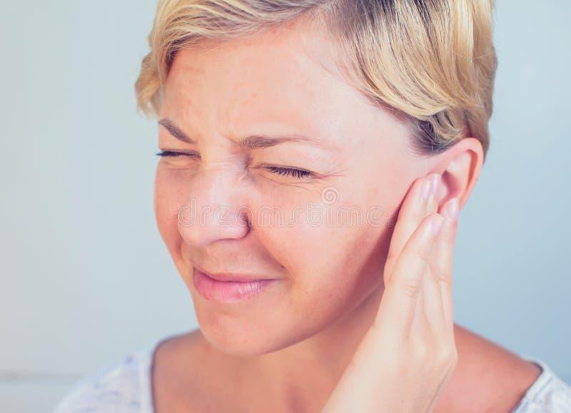 Jeune femelle ayant le mal d'oreille de douleur aux oreilles photos libres de droits