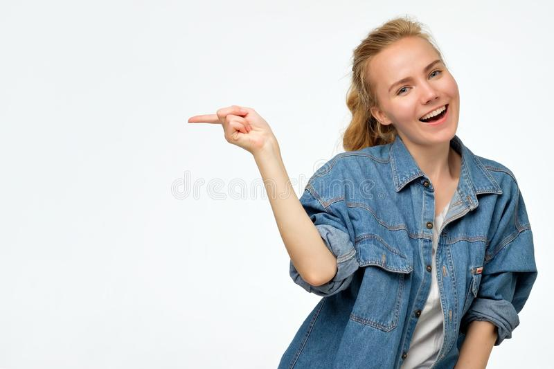 Jeune femelle blonde montrant quelque chose intéressante au mur de l'espace de copie image stock