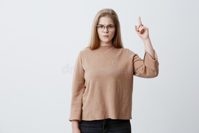 Jeune femelle caucasienne fâchée et indignée avec les cheveux blonds et les lunettes recherchant et dirigeant l'index vers le hau photo stock