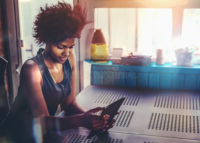 Jeune femelle d'Afro à la table avec le PC de comprimé photographie stock