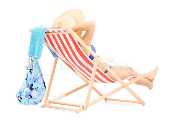 Jeune femelle dans le bikini se trouvant sur une chaise de plage photographie stock