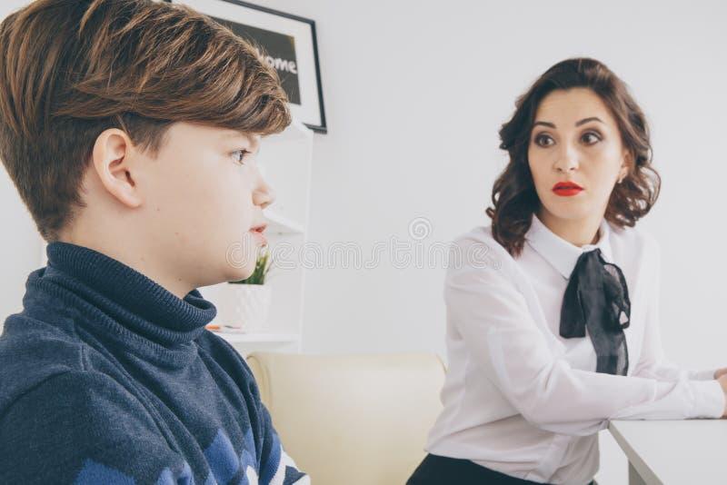 Jeune femelle de brunnette parlant au garçon d'intérieur la salle blanche Femme de psychologue avec patiant Thérapie de psycholog photographie stock libre de droits