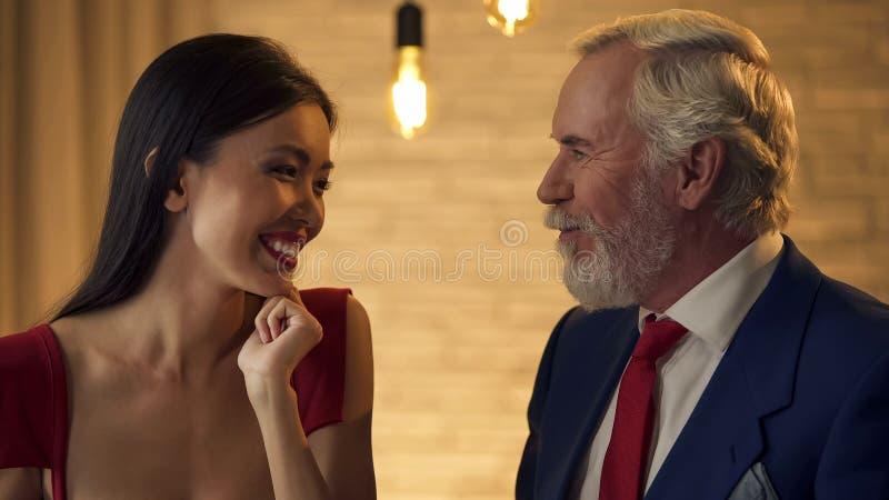 Jeune femelle de sourire et homme plus âgé se regardant avec amour, date romantique photos libres de droits