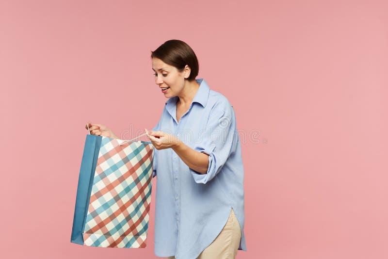 Jeune femelle enthousiaste dans le casualwear regardant la surprise dans le sac en papier ouvert photographie stock