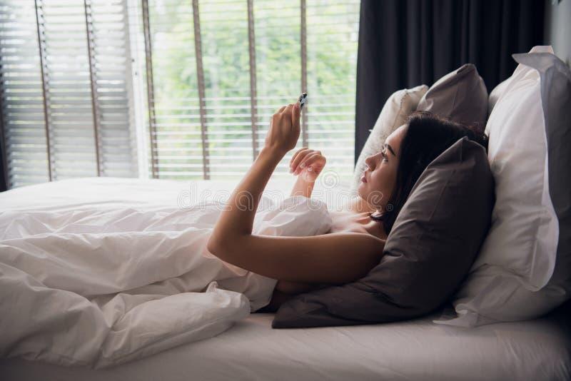 Jeune femelle européenne attirante heureuse souriant largement tout en lisant le message textuel de son ami à l'aide du téléphone images stock