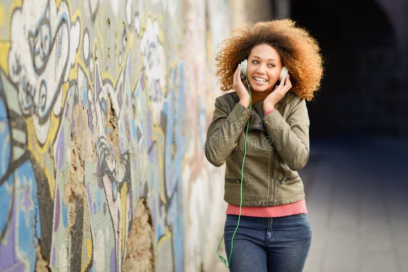 Jeune femelle noire attirante à l'arrière-plan urbain images stock