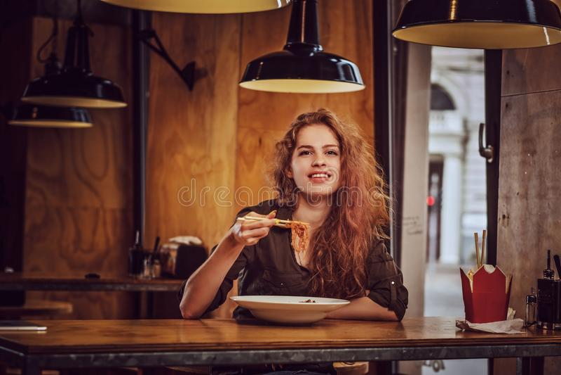 Jeune femelle rousse mangeant les nouilles épicées dans un restaurant asiatique photo stock