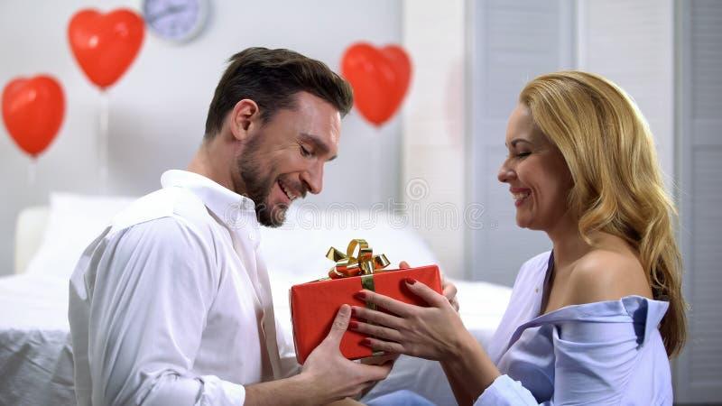 Jeune femelle séduisante donnant le boîte-cadeau rouge à l'ami étonné, anniversaire image stock