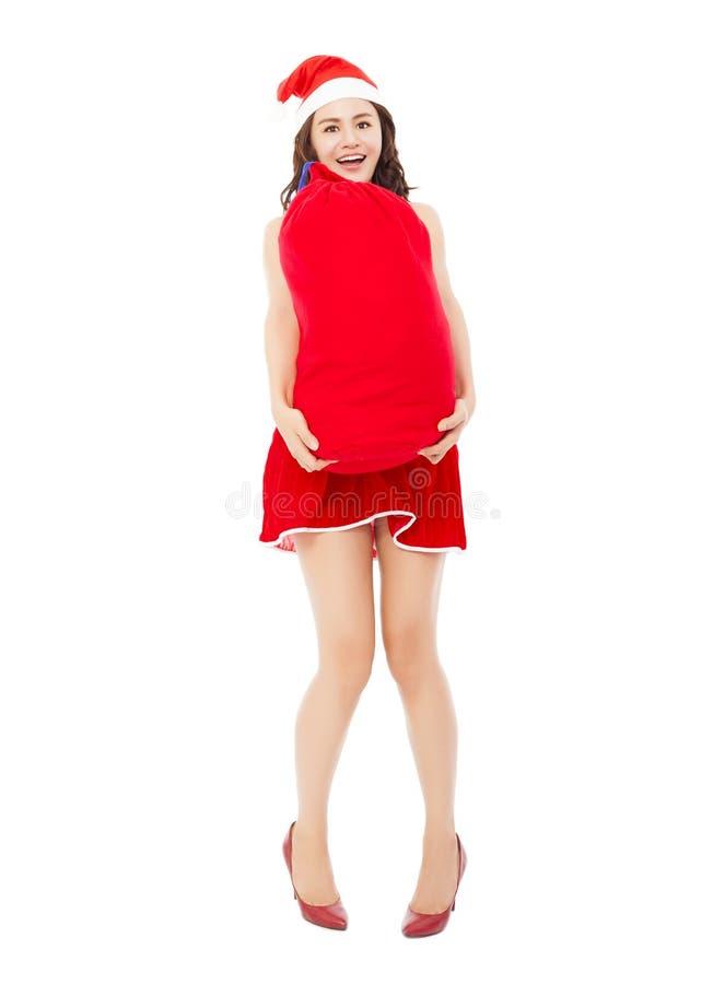 Jeune femelle tenant un sac lourd de cadeau avec le costume de Noël image libre de droits