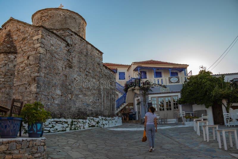 Jeune femme à côté de vieille église typique à une place dans une petite ville grecque de Chora en Grèce pendant l'été, partie o  image stock