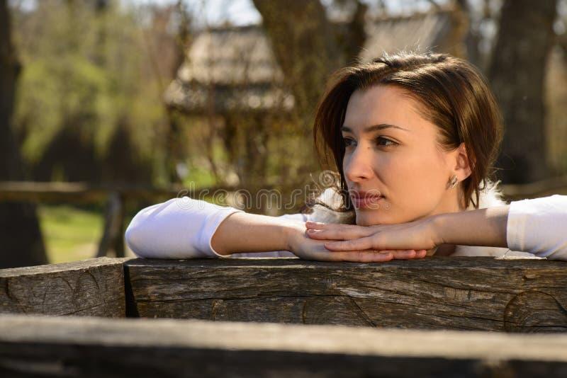 Jeune femme à côté d'un puits en bois photographie stock libre de droits