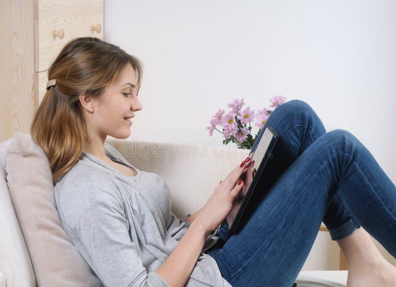 Jeune femme à l'aide d'un comprimé numérique tout en se reposant sur le sofa à images libres de droits