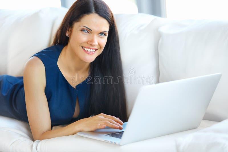 Jeune femme à l'aide d'un ordinateur portable tout en détendant à la maison photographie stock libre de droits