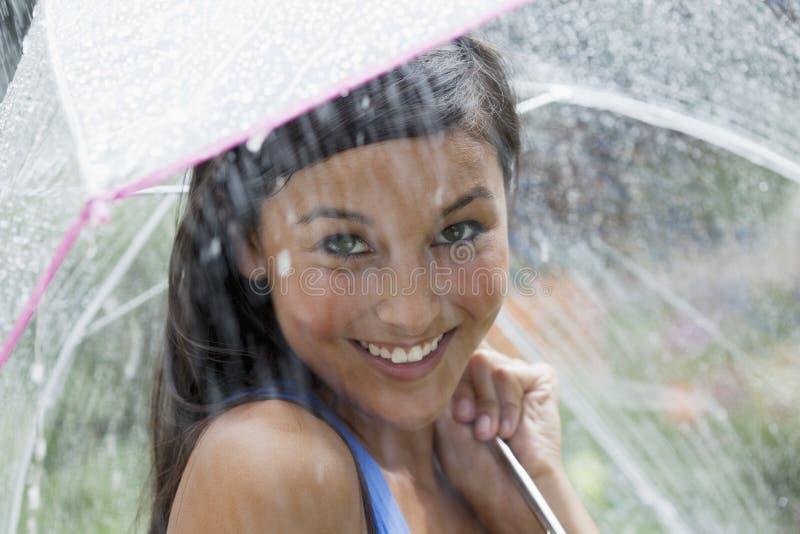 Jeune femme à l'aide d'un parapluie sous la pluie photographie stock libre de droits