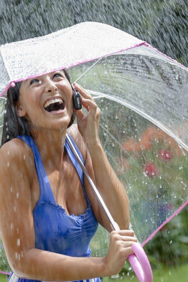 Jeune femme à l'aide d'un portable et d'un parapluie sous la pluie photographie stock libre de droits