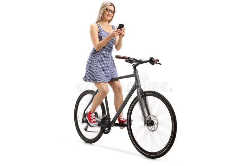 Jeune femme à l'aide d'un téléphone et montant un vélo image stock