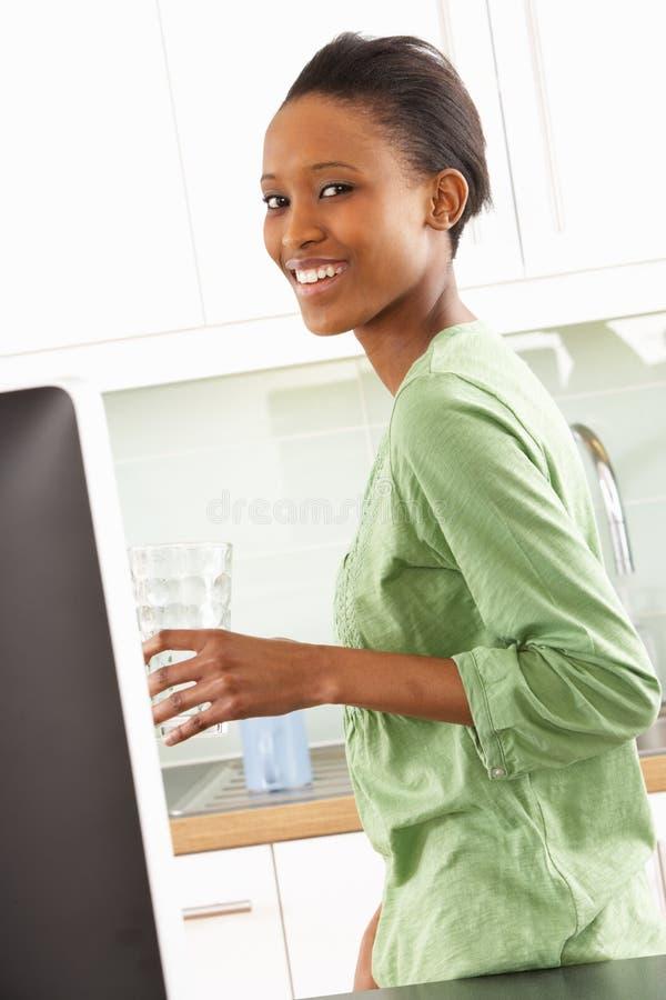 Jeune femme à l'aide de l'ordinateur dans la cuisine moderne image libre de droits