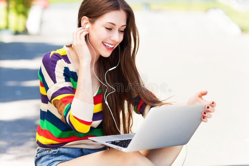 Jeune femme à l'aide de l'ordinateur portatif à l'extérieur images libres de droits