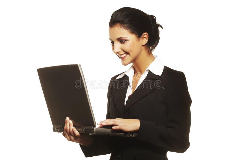 Jeune femme à l'aide de l'ordinateur portatif sur le fond blanc images libres de droits