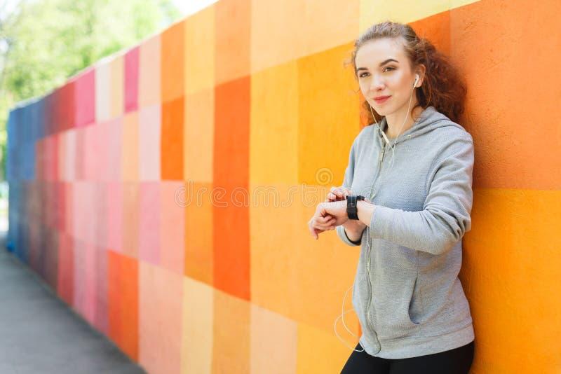 Jeune femme à l'aide de la montre intelligente, backgroud lumineux photographie stock libre de droits