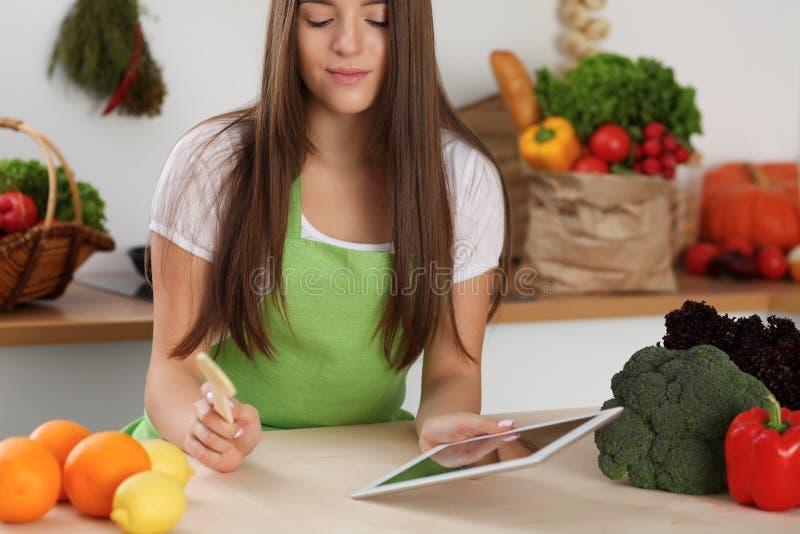 Jeune femme à l'aide de la tablette tout en faisant cuire dans la cuisine Householding, nourriture savoureuse et technologie numé image stock