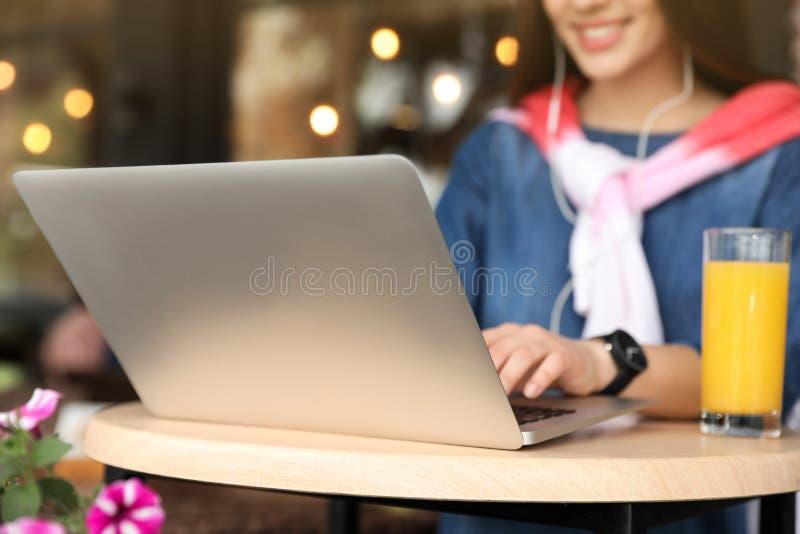 Jeune femme à l'aide de l'ordinateur portable à la table en café photo stock