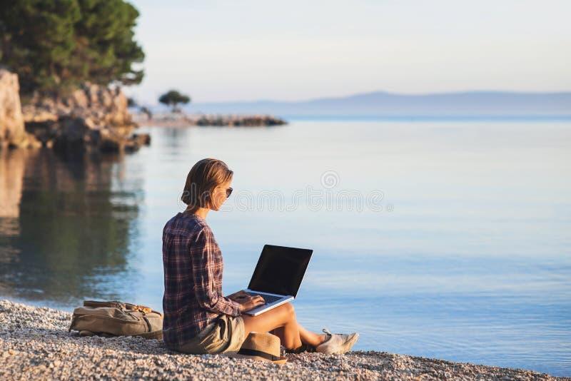 Jeune femme à l'aide de l'ordinateur portable sur une plage Travaillent en indépendants le concept de travail photos libres de droits