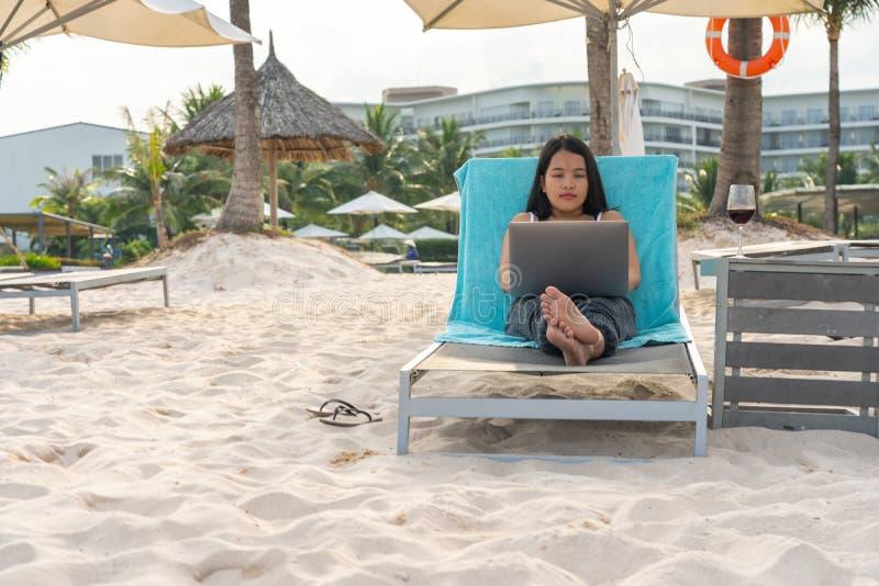 Jeune femme ? l'aide de l'ordinateur portable tout en d?tendant sur la plage images stock