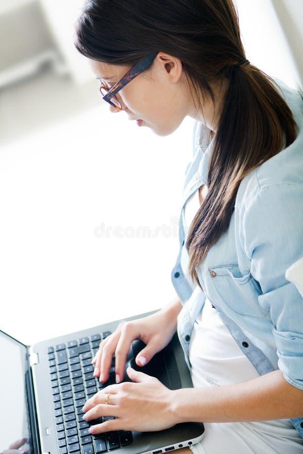 Jeune femme à l'aide de son ordinateur portable à la maison images libres de droits