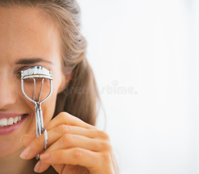 Jeune femme à l'aide du bigoudi de cil photos libres de droits