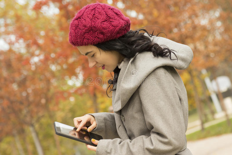 Jeune femme à l'aide du comprimé numérique au parc pendant l'automne photographie stock