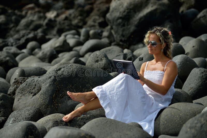 Jeune femme à l'aide du comprimé sur la plage rocheuse en été image libre de droits