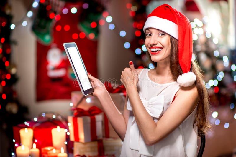 Jeune femme à l'aide du comprimé sur Noël photo stock