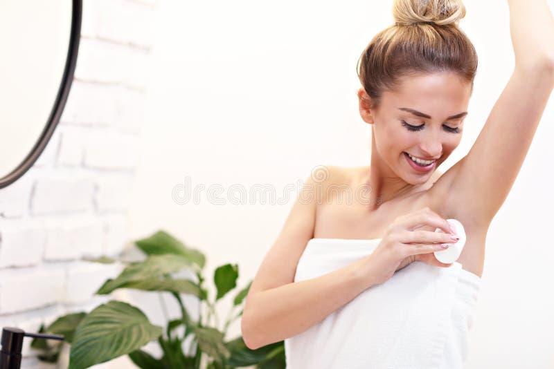 Jeune femme à l'aide du désodorisant dans la salle de bains photos stock
