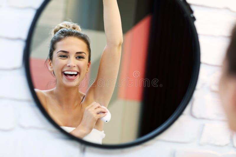 Jeune femme à l'aide du désodorisant dans la salle de bains photographie stock libre de droits