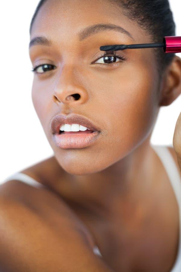 Jeune femme à l'aide du mascara pour ses cils photo libre de droits