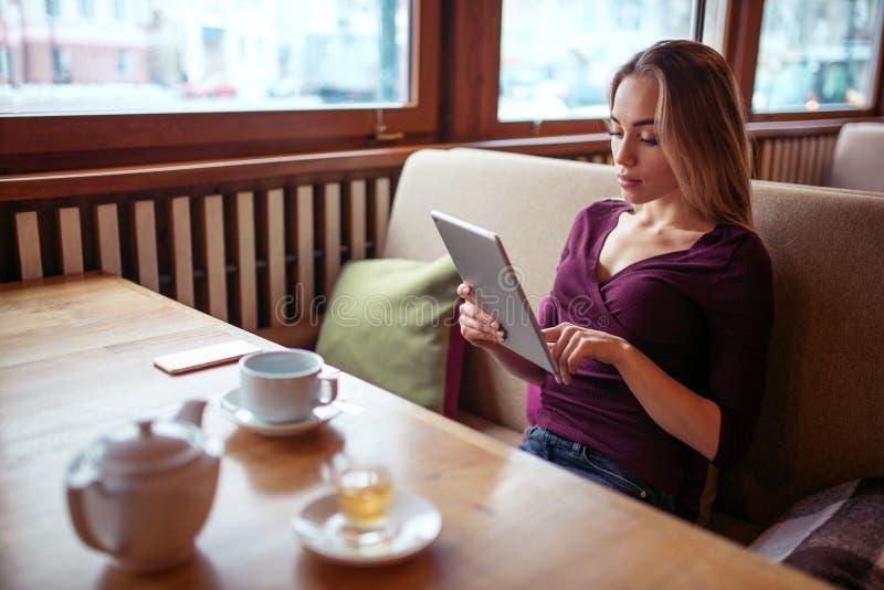 Download Jeune Femme à L'aide Du PC De Comprimé En Café Photo stock - Image du restaurant, connexion: 87700024